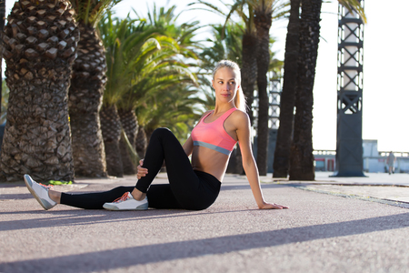 female jogger: Portrait of a young fit woman dressed in sportswear sitting on the road and resting after morning running in the fresh air, pretty female jogger with slender figure taking break after workout outdoors