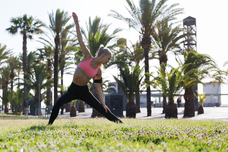 warm up: Full length portrait of fitness woman enjoying her outdoors warm up while listening to music in headphones, female runner stretching her body before begin morning run in the park in sunny summer day