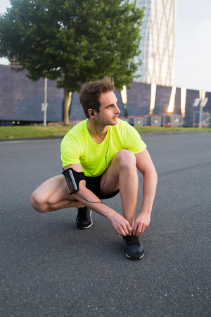 run down: Full length portrait young man sat down on the road to tie laces on his sneakers and is ready to run in morning, sportsman with armband on the arm rest after run while listening to music in headphones