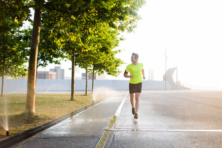young male: Young male jogger running on the road along beautiful green park while listen to music in headphones on his smart phone, male sports structure runs outdoors in sunny morning while using modern device