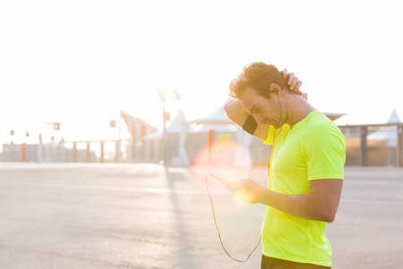 armband: Male runner is uses a mobile phone to switch music on the playlist with copy space for text advertising, young sportsman stopped on the road after an active run while listening to music in headphones Stock Photo