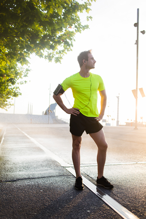 green technology: Full length portrait of male runner resting after workout outdoors while enjoying beautiful sunrise in summer morning, handsome athletic man taking break after run outside in park while looking away Stock Photo