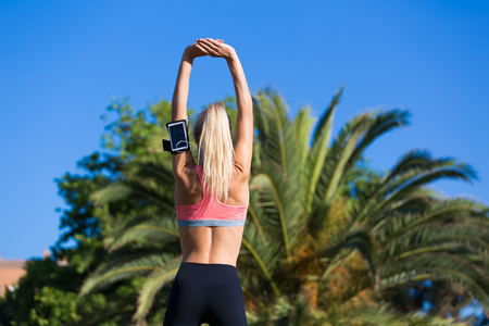 female jogger: Young female jogger with running armband on the arm working out outdoors in sunny summer day, fit woman dressed in sportswear with perfect slender figure doing stretching exercise in beautiful park