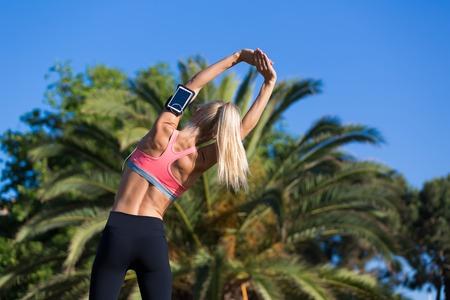 female jogger: Vista trasera de tiro de corredor de mujer joven vestida con ropa deportiva haciendo ejercicios de estiramiento al aire libre en d�a soleado de verano, adaptarse cauc�sica mujer witn cuerpo perfecto ejercicio en palmeras aparcar fuera