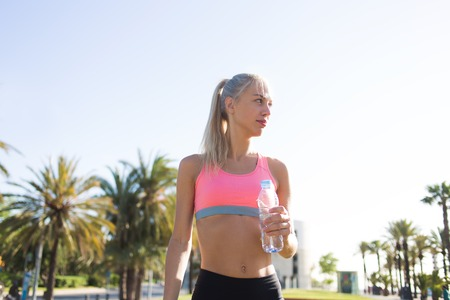 personas tomando agua: Half length portrait of female runner with slender figure holding water bottle while resting after a morning jog in the park, sports woman taking break after training with copy space sky background