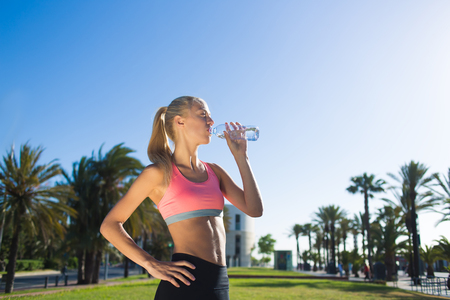 athletic wear: Half length portrait of tired athletic woman dressed in sport wear refreshing with energy drink after jog, female runner drink water against blue sky background with copy space area for text message
