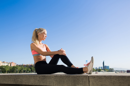 enjoys: Tired female jogger taking break after fitness training while sitting on pier against blue sky background with copy space area for advertising, young sports woman enjoys resting after workout outdoors Stock Photo