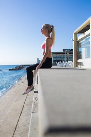 female jogger: Young fit woman with eyes closed enjoying the rest and morning sun rays after workout outdoors, female jogger relaxing after active physical exercise near the beach with copy space for text or content Foto de archivo