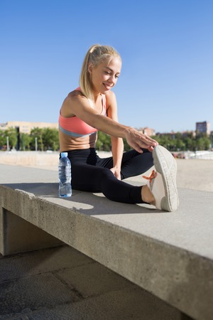 water well: Portrait of a smiling athletic female with slender body performs stretching before jogging in sunny summer day, beautiful fit woman dressed in sport bra doing warm up exercises in the fresh air