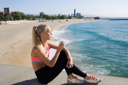 female jogger: Fit women refreshing with energy drink after workout outdoors while sitting against sea background with copy space area for your text message or content, young female jogger enjoys rest after training