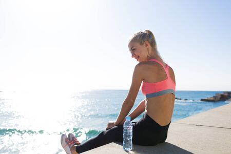 break out: Young smiling female enjoying rest after physical training while sitting against sea at sunny morning, athletic woman taking break after workout with copy space area for your text message or content