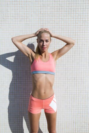 half dressed: Half length portrait of tired fit woman dressed in sport bra and shorts taking break after physical activity standing against street wall in sunny day, female jogger resting after workout outdoors