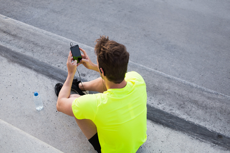runner: Rear view of male runner in bright t-shirt using mobile phone while taking break after active intense training outdoors, young sports man use smart phone with blank copy pace screen for text message