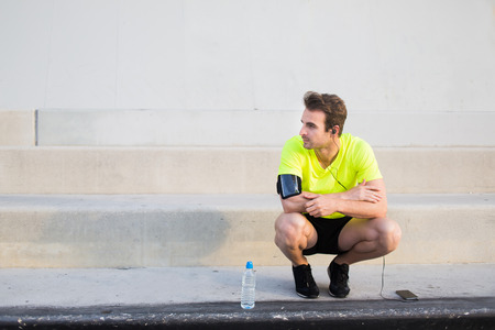 runner up: Caucasian male runner looking to the copy space area for your text while having a rest after workout training, male runner listen to music in headphones though cell phone and admiring city landscape Stock Photo