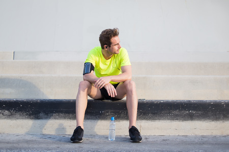 personas tomando agua: Full length portrait of young sports man thoughtful looking away while taking break after workout training outdoors, male runner listen to music in headphones while admiring morning sunrise in summer