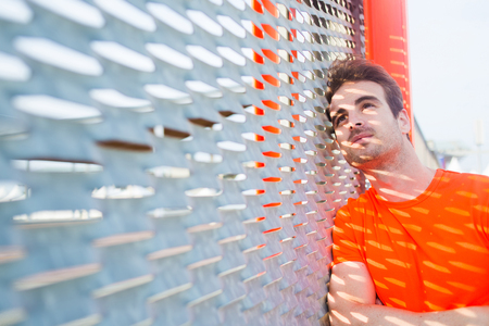 metal fence: Portrait of caucasian sad man leaning on metal fence with hands crossed looking thoughtful, young caucasian male runner taking break after active training with copy space area for text your message