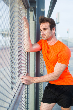 metal fence: Portrait of caucasian sports man standing near metal fence thoughtful looking away while rest, young caucasian male runner taking break after active training with copy space area for text your message Stock Photo