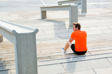 rest: Young sportsman resting after an active fitness training sitting on the steps in urban setting, male runner enjoying city view while taking break after workout outdoors, athletic men having rest Stock Photo