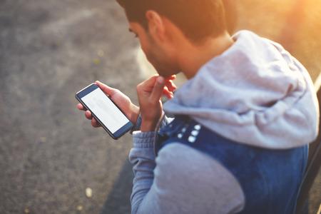 juventud: Cierre de joven apuesto mediante tel�fono m�vil mientras est� de pie al aire libre en la tarde soleada Foto de archivo