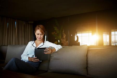 Empresaria encantadora que lee el blog femenino en una red social a través de la almohadilla táctil mientras se espera para el menú en la cafetería moderna Foto de archivo
