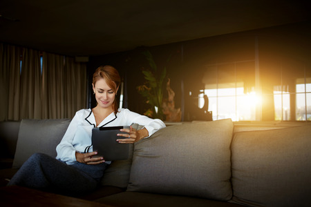mujer elegante: Empresaria encantadora que lee el blog femenino en una red social a través de la almohadilla táctil mientras se espera para el menú en la cafetería moderna
