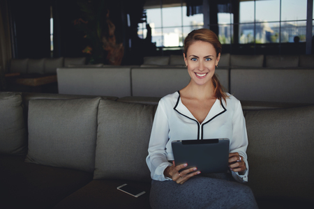 good mood: Beautiful smiling woman looking at camera while sitting with touch pad in modern coffee shop interior, female in good mood using digital tablet while waiting for her order in comfortable restaurant