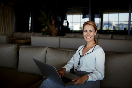 restaurateur: Smiling young businesswoman looking at camera while holding on her knees open laptop computer, beautiful female in good mood working on net-book while waiting for order in modern restaurant interior