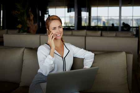restaurateur: Smiling woman owner talking on mobile phone with client while sitting with laptop computer in her restaurant, female having pleasant conversation on cell telephone while holding on knees net-book Stock Photo
