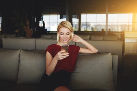 nouvelles lecture femme magnifique via le réseau sur téléphone mobile en attendant sa commande dans un café moderne, femme européenne sur la recherche d'information téléphone cellulaire alors qu'il était assis dans l'intérieur restaurant Banque d'images