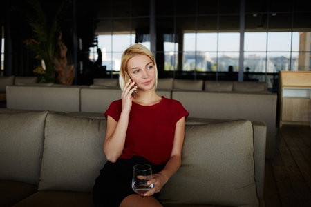 restaurateur: Young woman owner calling with cell telephone while waiting to the meeting with designer, beautiful female restaurateur holding glass of fresh water and phoning via mobile phone while sitting in cafe Stock Photo