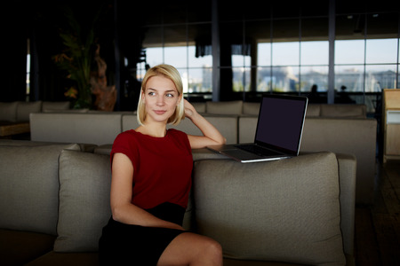 restaurateur: Dreaming woman sitting in restaurant interior near laptop computer with copy space screen for your text message, female thinking about something good while rest after video conversation on net-book