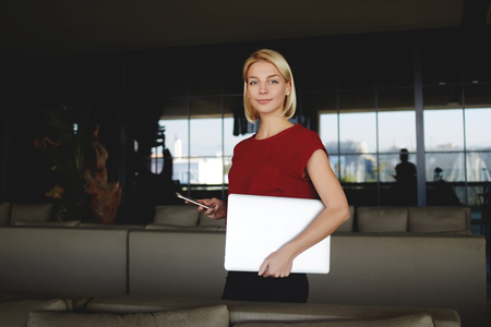 Woman holding mobile phone and laptop computer with copy space for your brand while standing in office interior, female entrepreneur posing with cell telephone and net-book after successful meeting