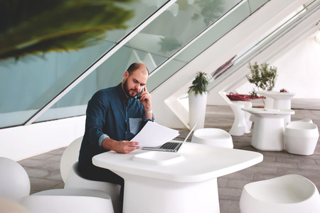 netbook: Young businessman with paper documents and open net-book decides important issues via cell telephone while sitting in office interior, male entrepreneur talking on mobile phone during reviewing resume