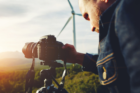 geodesist: Young man photographing beautiful calm wild nature with camera of while standing against wind turbine, male professional geo-desist measures the distance on theodolite for build a new housing estate Stock Photo