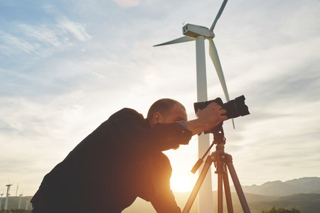geodesist: Silhouette of a man geo-desist measures the distance on theodolite for building new highway, male professional photographer taking photo on digital camera while standing against windmill and sunset