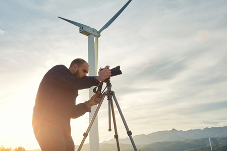 teodolito: Hombre profesional geo-desista mide la distancia en teodolito para la construcción de centro de negocios, joven fotógrafo masculino graba vídeo en la cámara digital mientras está de pie en contra de la turbina de viento en el campo