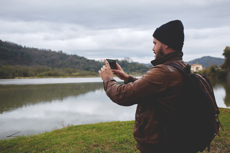 taking video: Young hipster guy taking photo on his mobile phone camera of a beautiful landscape while standing near lake, bearded man shoots video on cell telephone during amazing travel through the countryside Stock Photo