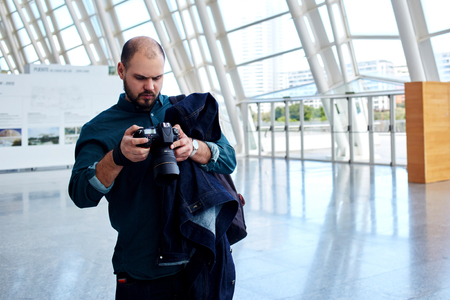 proffesional occupation: Male traveler browsing images on professional digital camera after vacation holidays while walking in modern airport hallway, young man photographer looking at the pictures from the last photo session Stock Photo