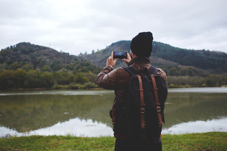 taking video: Back view of a man tourist shoots video with beautiful nature landscape on cell telephone during his autumn adventure, stylish hipster guy with a rucksack on his back taking photo on cell telephone Stock Photo