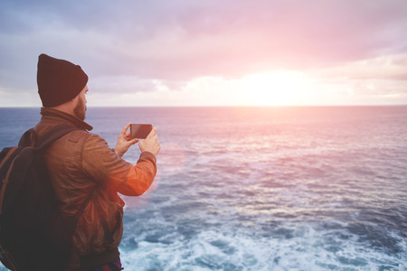 taking video: Back view of a young man tourist taking photo with cell telephone digital camera while standing in front sea with waves, hipster guy with trendy look shoots video with ocean landscape on mobile phone Stock Photo