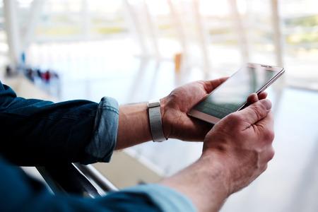 男の両手の中に立って携帯電話ショッピング センター、近代的な空港ホールで誰かを待っている間、携帯電話経由でワイヤレスに接続する若い男性