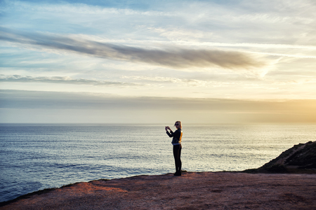 taking video: Silhouette of female taking photo of beautiful sea landscape on mobile phone camera while standing on mountain rock, young woman shoots video of an amazing scenery view of calm ocean on cell telephone