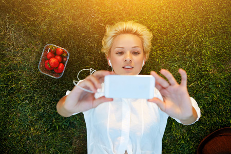 grass plot: Top view of pretty young woman making self portrait on mobile phone while resting on grass plot in summer day, attractive female student taking picture with cell telephone camera while lying on a lawn Stock Photo