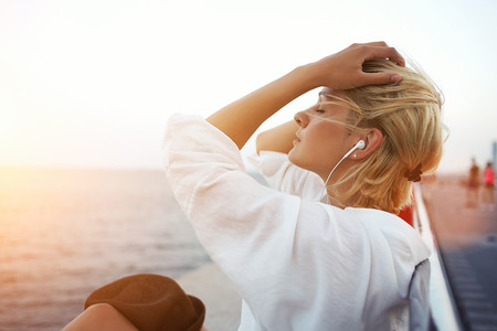 prettiness: Beautiful blonde hair woman listening to music or radio in headphones while enjoying warm summer evening, pretty hipster girl with closed eyes resting on pier near sea during her long-awaited vacation Stock Photo