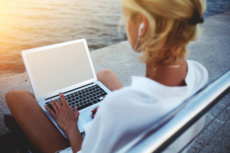 work on computer: Back view of female using net-book with blank copy space screen for your text message or promotional content, young woman reading news via laptop computer while sitting near sea during her vacations