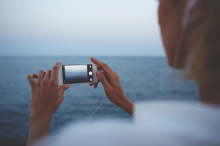 hands free device: Closeup image of young female photographing sea landscape on mobile phone while strolling on the beach, woman taking picture on cell telephone camera while enjoying her weekend vacation overseas Stock Photo