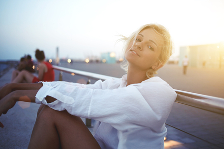 prettiness: Young beautiful woman posing while sitting on a sea pier in warm summer evening during weekend, charming European female enjoying rest and good day while relaxing outdoors during recreation time