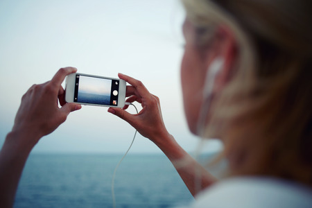 taking video: Cropped shot view of woman shoots video of sea landscape on cell telephone during walking on the beach, female taking photo of ocean view with mobile phone camera and listening to music in headphones