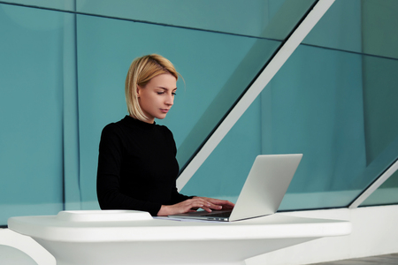 searching information: Concentrated woman developer performs software engineering on net-book while sitting in office interior, young businesswoman searching information in internet via laptop computer during work break Stock Photo