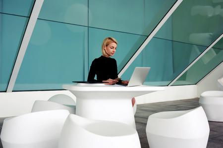 mujer trabajadora: Mujer exitoso empresario que espera una llamada en el teléfono móvil mientras se está sentado con red de a libro abierto en la oficina entre otras, economista femenina que sostiene el teléfono celular en la mano durante el trabajo en el ordenador portátil Foto de archivo